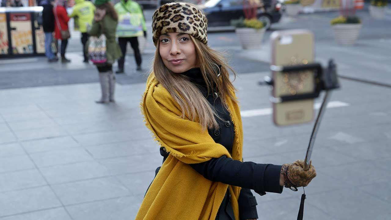 Sandy Johal uses a selfie stick to take a picture of herself in Times Square in New York, Thursday, Jan. 8, 2015