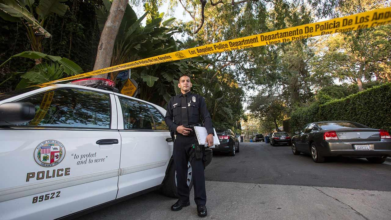 An officer stands outside a home in the Hollywood Hills, Tuesday, March 31, 2015. Police say a man was found dead at the home of Andrew Getty, heir to Getty oil fortune.