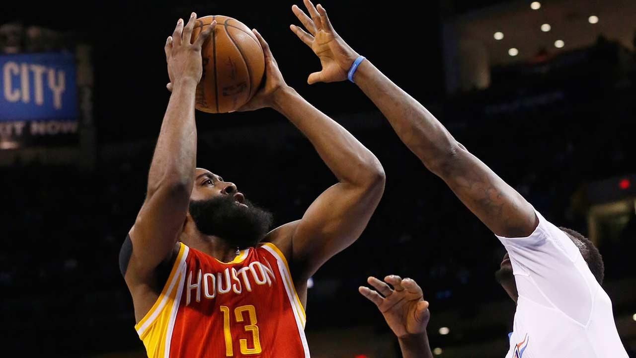 Houston Rockets guard James Harden (13) shoots in front of Oklahoma City Thunder center Steven Adams, center, and guard Anthony Morrow, right, in the first quarter of the game.