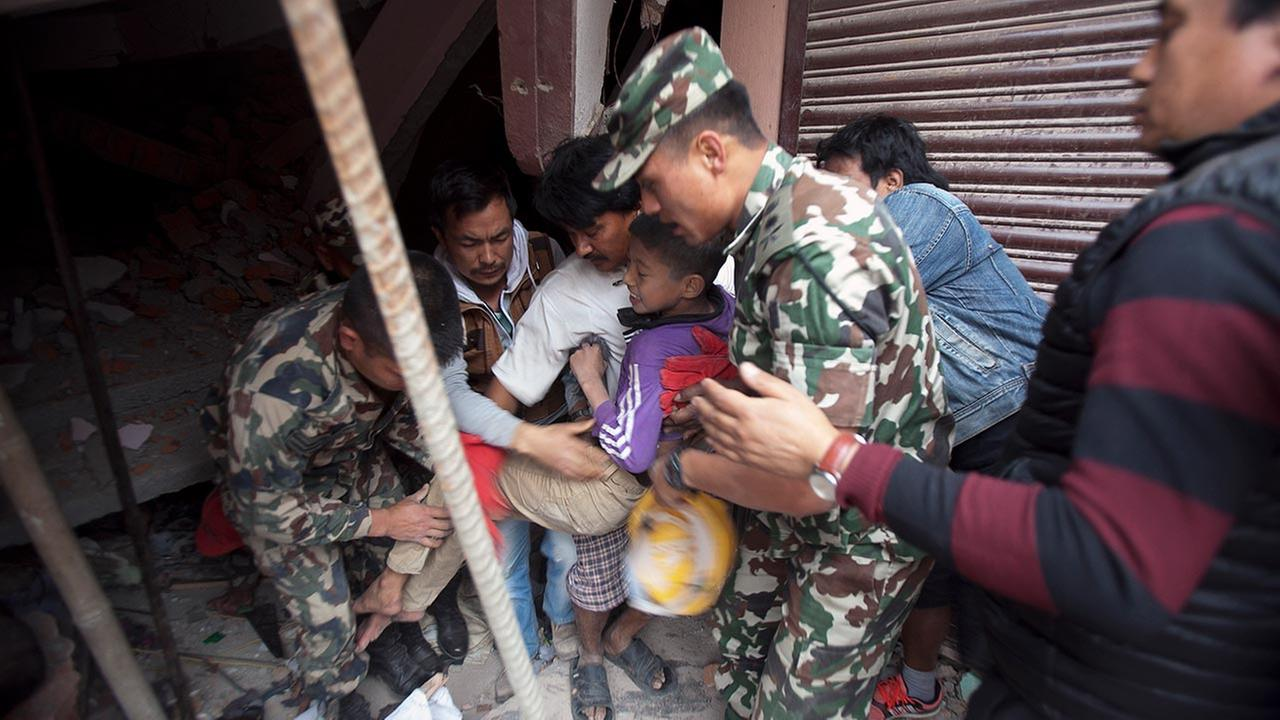 Volunteers carry an injured boy after rescuing him from the debris of a building that was damaged in an earthquake in Kathmandu, Nepal, Saturday, April 25, 2015