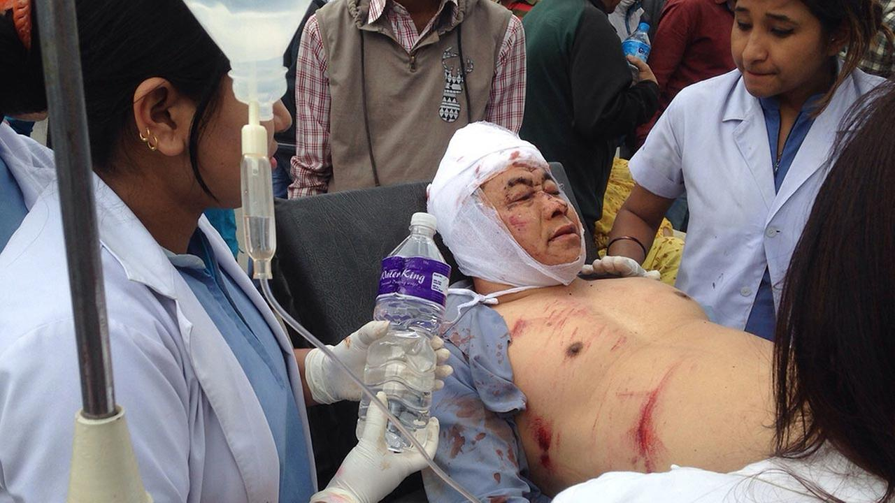 An injured person receives treatment outside the Medicare Hospital in Kathmandu, Nepal, Saturday, April 25, 2015