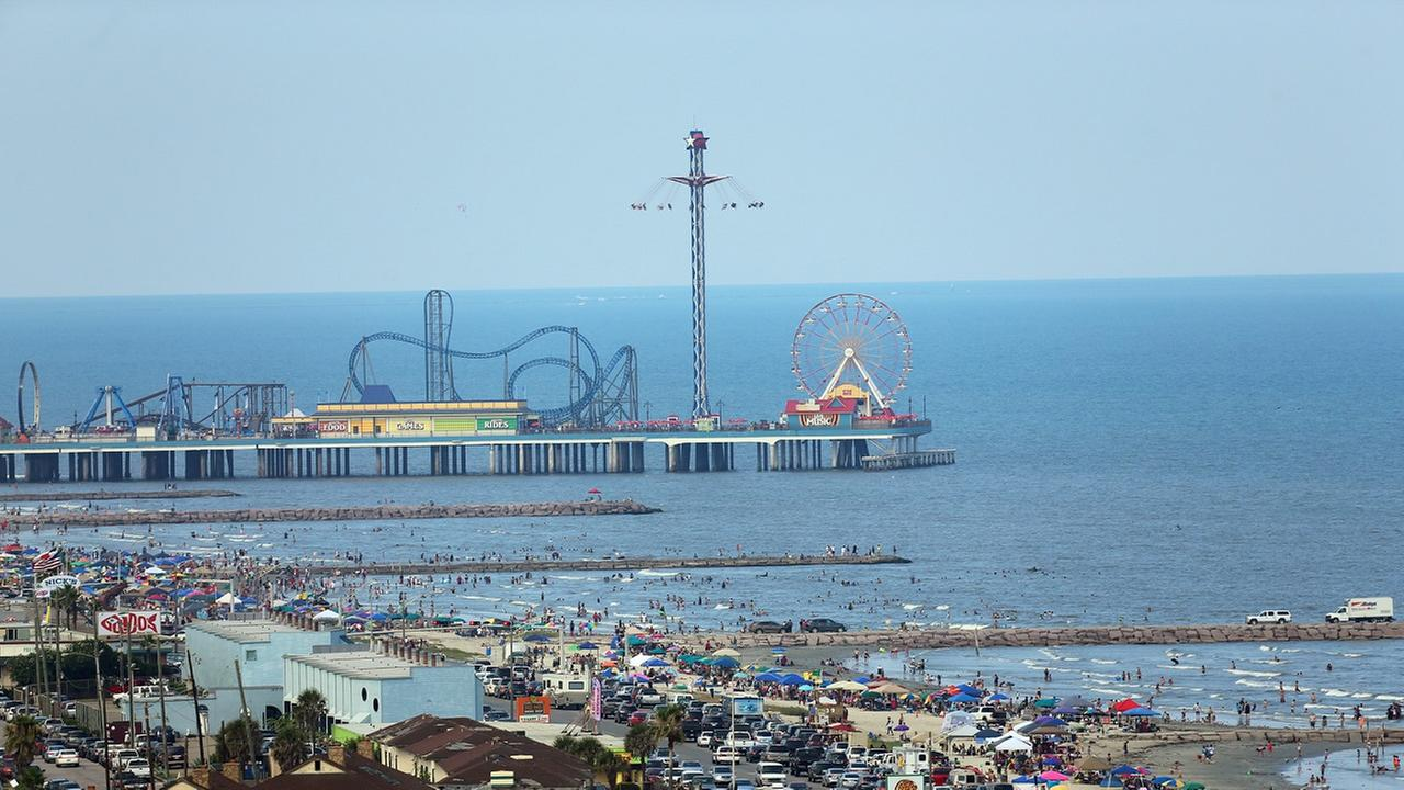 The Historic Pleasure Pier amusment park, seawall, and beaches of Galveston Island, Texas are seen from atop the San Luis Resort