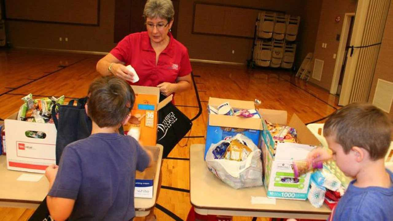 Jill Parks helps two young volunteers stuff backpacks for Sacks for Soldiers at the LDS Church stake in Eagle Springs June 12, 2015.