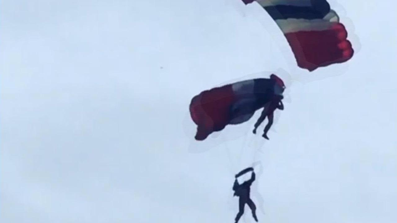 Image taken from video provided by Ricky Parnaby shows a member of the British military stunt team, The Red Devils, receiving assistance from a teammate after his parachute failed.