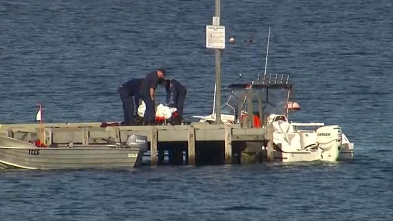 Police carry a body in a bag and place it in on a stretcher on a jetty in Triabunna,