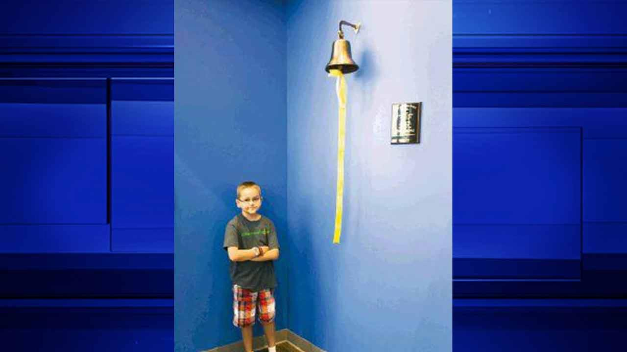 Ethan Williamson stands proudly next to the end of treatment bell after being the first patient to ring the new addition to Texas Childrens Cancer Center.