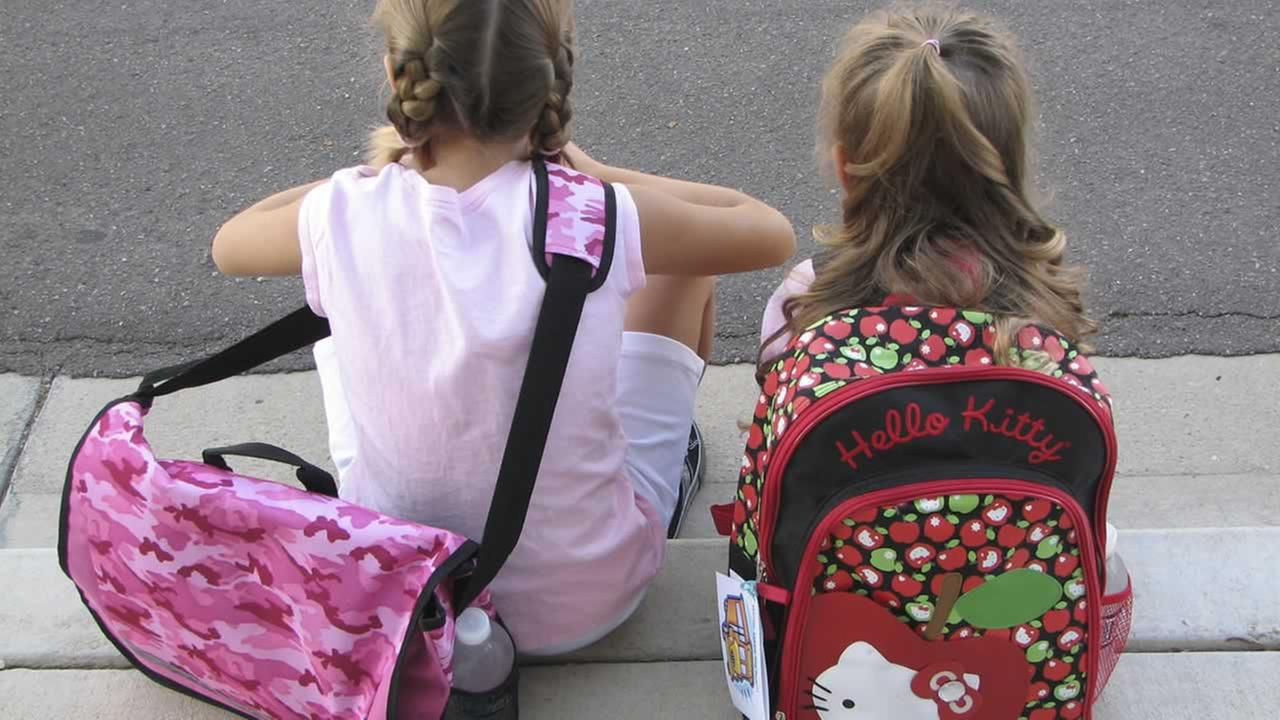 This undated photo provided by Rebecca Wilson shows her daughters Alex, 9, left, and Winter, 5, showing off their new backpacks for a new school year. (AP Photo/Rebecca Wilson)