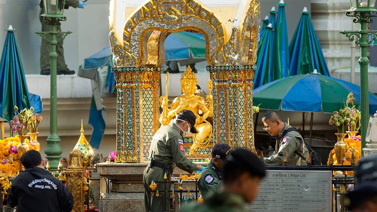 Police investigators work near the statue of Phra Phrom, which is the Thai interpretation of the Hindu god Brahma, at the Erawan Shrine the morning after an explosion in Bangkok