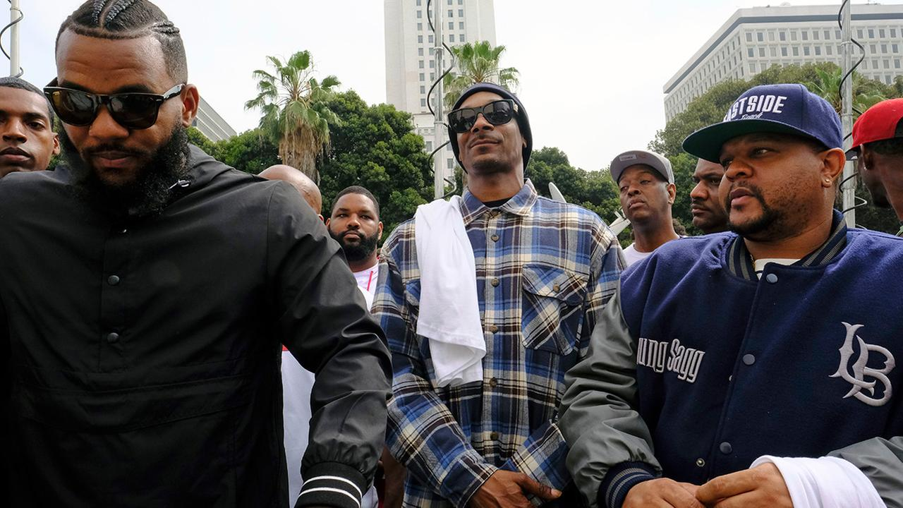 Rappers The Game, left, and Snoop Dogg, center, appear at a peaceful unification march outside of the graduation ceremony for the latest class of Los Angeles Police recruits.