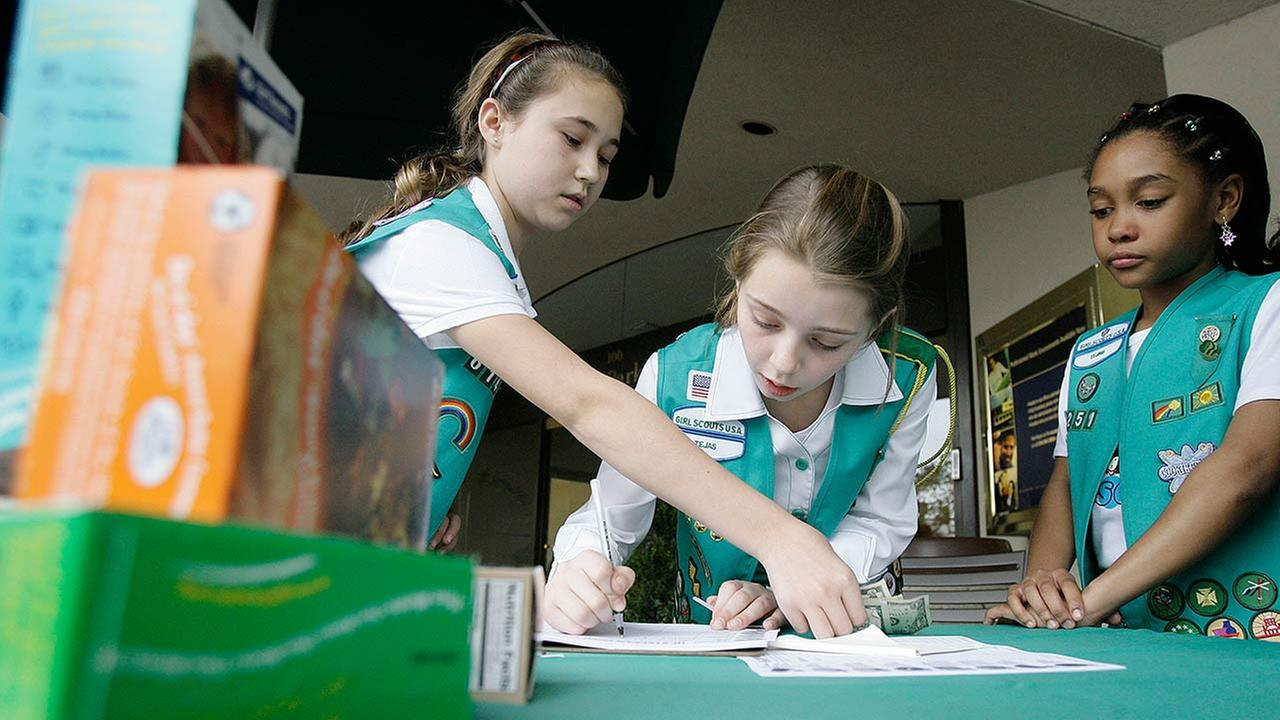Girl Scouts fill out an order form while selling Girl Scout cookies in Dallas