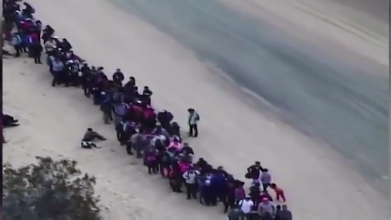 Video shows group of 376 migrants who entered the US in an area already protected by a fence.
