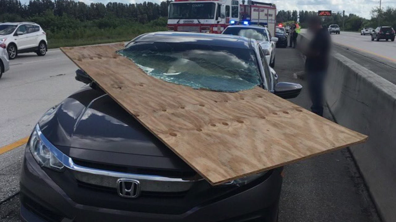Driver walks away uninjured after plywood impales windshield