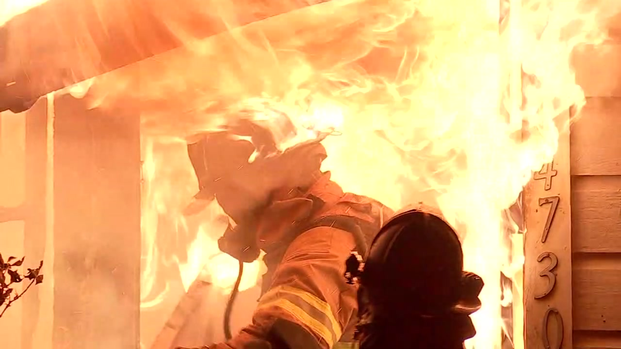 (File) A firefighters hat catches on fire while fighting an apartment fire in an undated file photo.