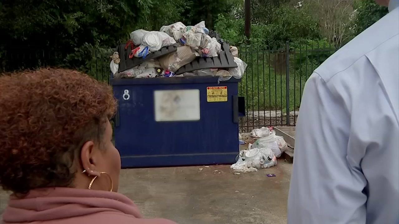 A pile of garbage sits on top of a dumpster outside the Wellsprings Village womens center.