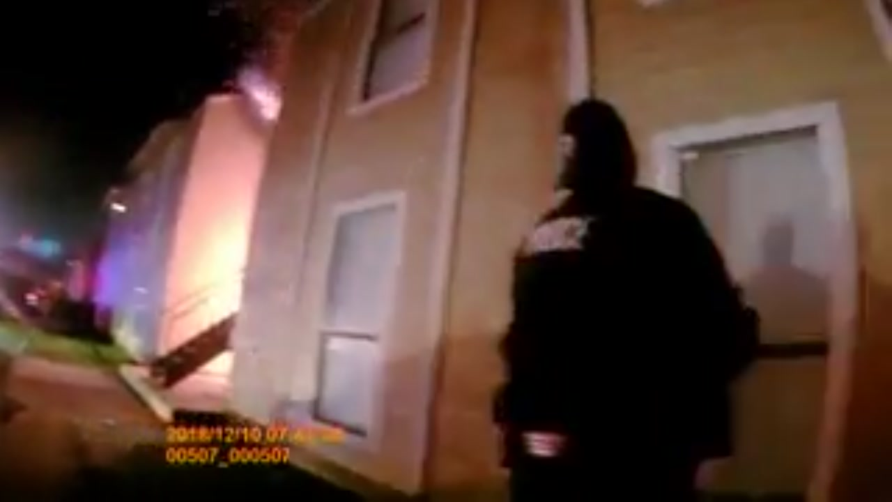 Police officers catch boy as he jumps from 2nd story window during apartment fire.