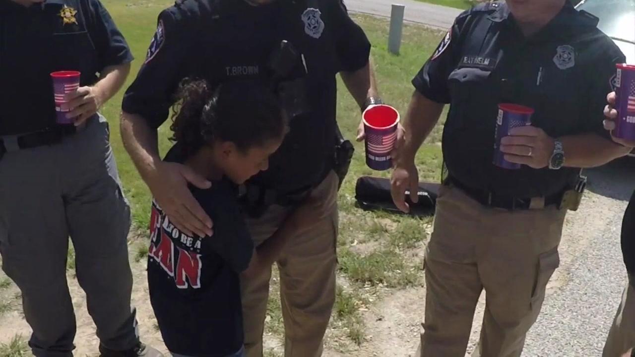 Girl serves officers lemonade