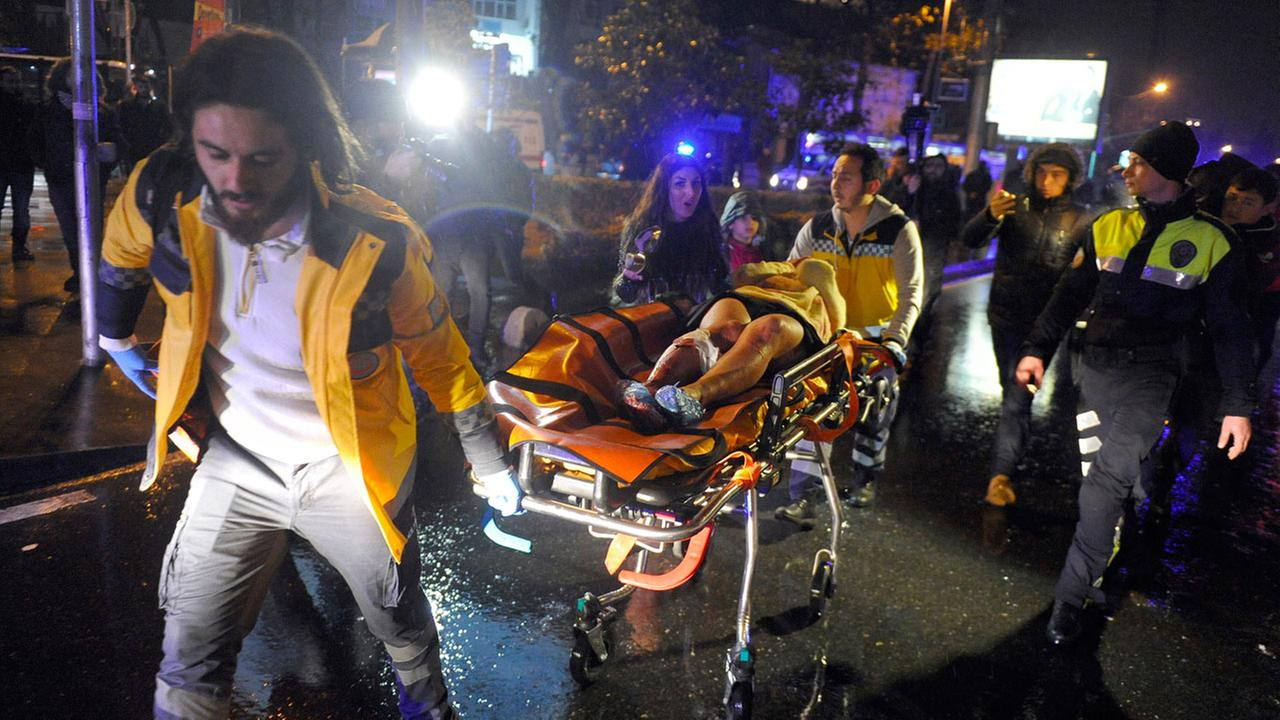 Medics carry a wounded person at the scene after an attack at a popular nightclub in Istanbul, early Sunday, Jan. 1, 2017.