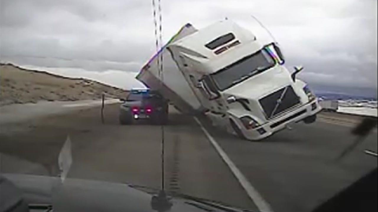 VIDEO: Wind tips 18-wheeler on top of patrol car