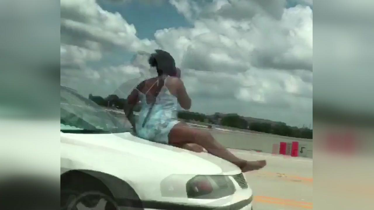 Woman rides on hood of car on Highway 290 in Houston