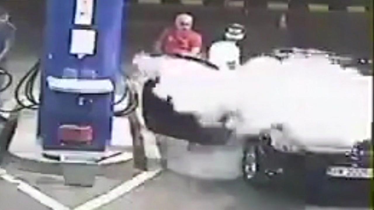 Gas station attendant sprays extinguisher on man smoking