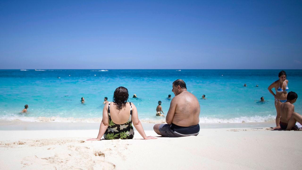 Tourists sunbathe along the beach in Nassau, Bahamas.