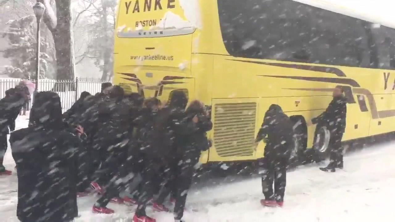 Womens college basketball team pushes buses in snow