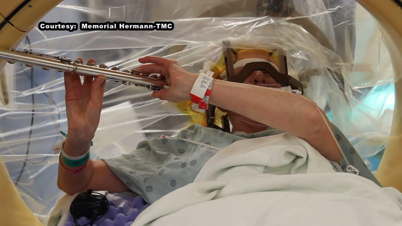 Woman plays the flute while surgeons operate on her brain