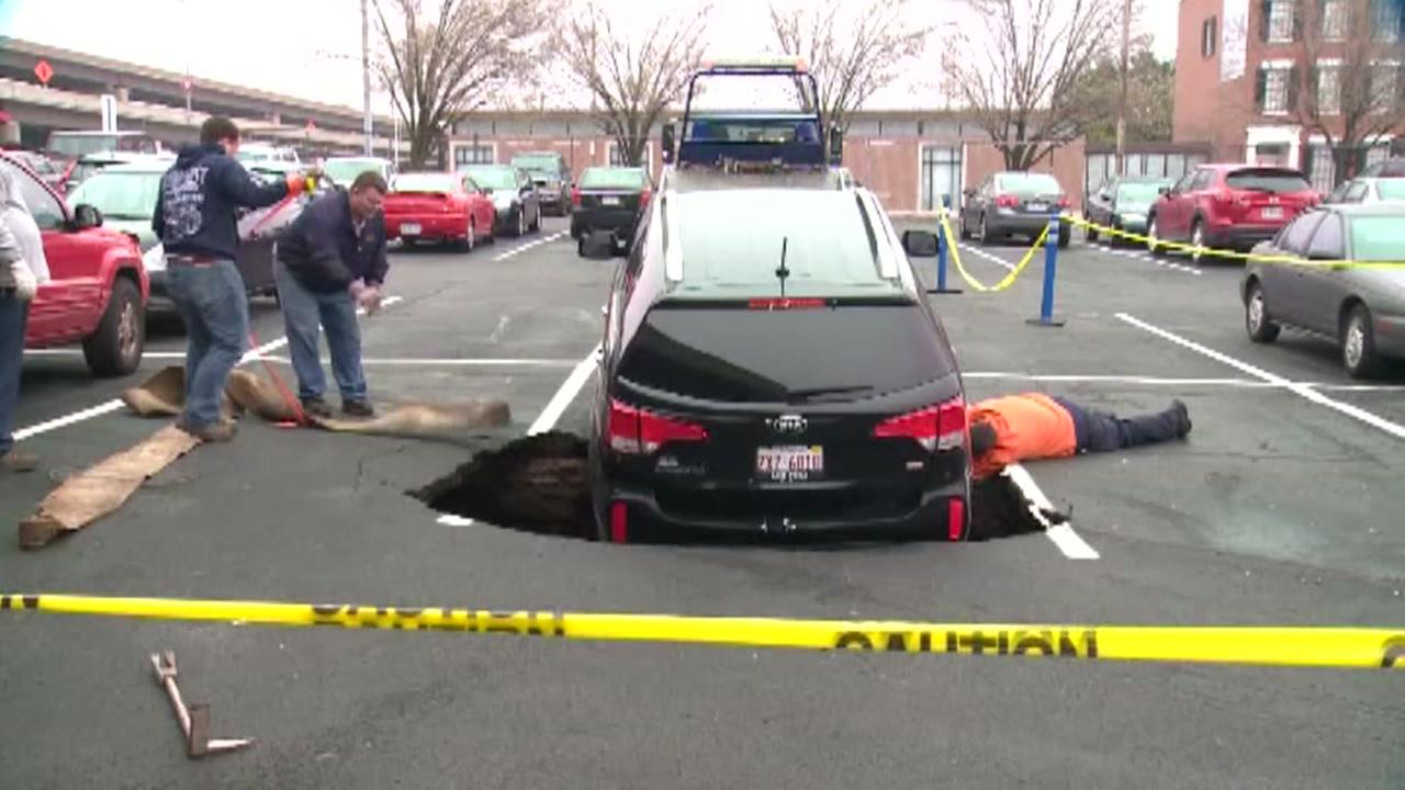 TV station workers vehicle stuck in sinkhole