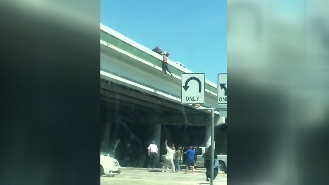 Good Samaritans scramble to save man dangling from overpass
