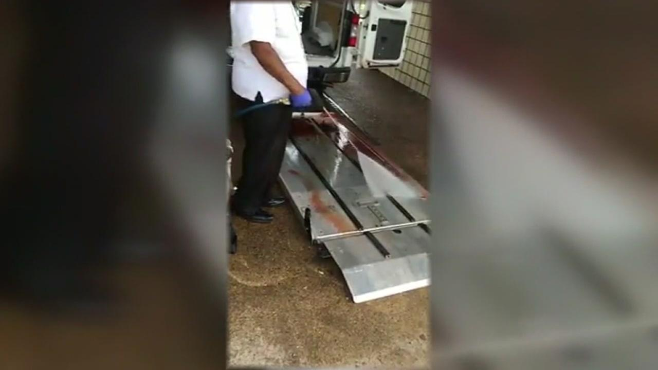 Funeral home employee seen washing red liquid from van at a public car wash