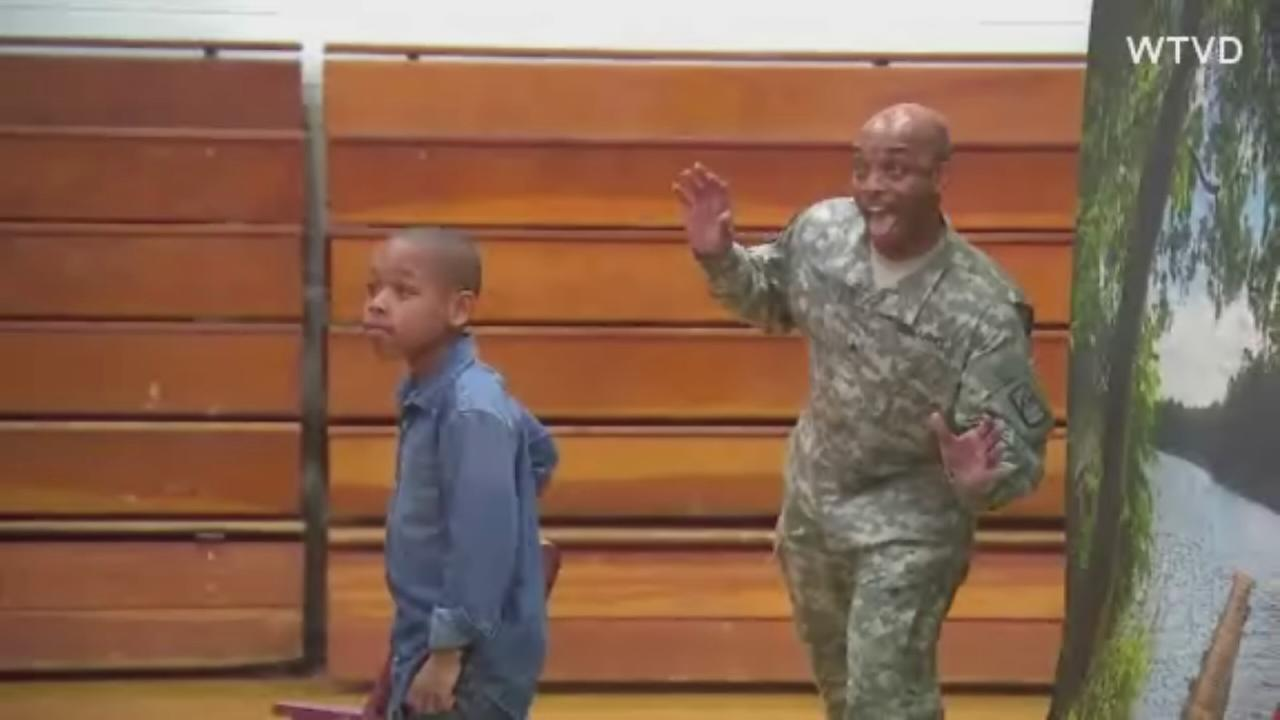Solder dad surprise photobombs son