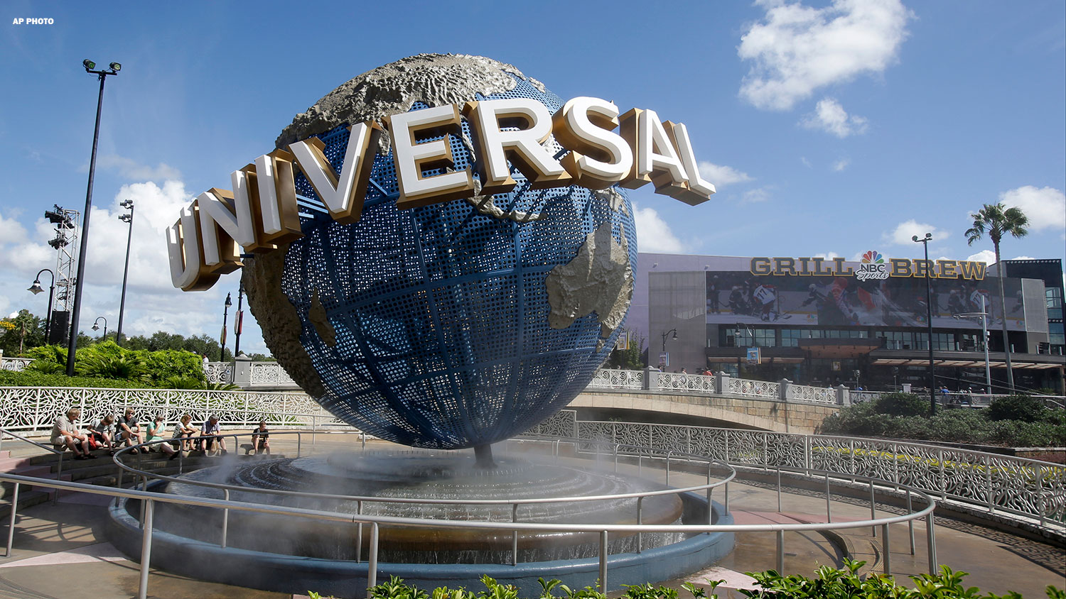 FILE-In this Thursday, Oct. 22, 2015 file photo, park guests relax and cool off with a water mist under the globe at Universal Studios City Walk in Orlando, Fla.