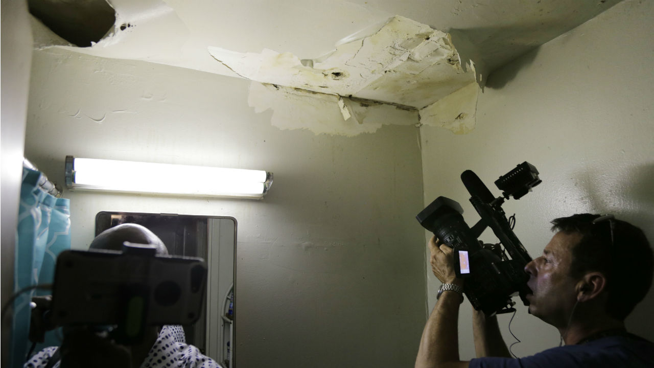 Reporters inspect peeling paint and mold in the bathroom of a NYCHA apartment in New York, Tuesday, July 3, 2018.