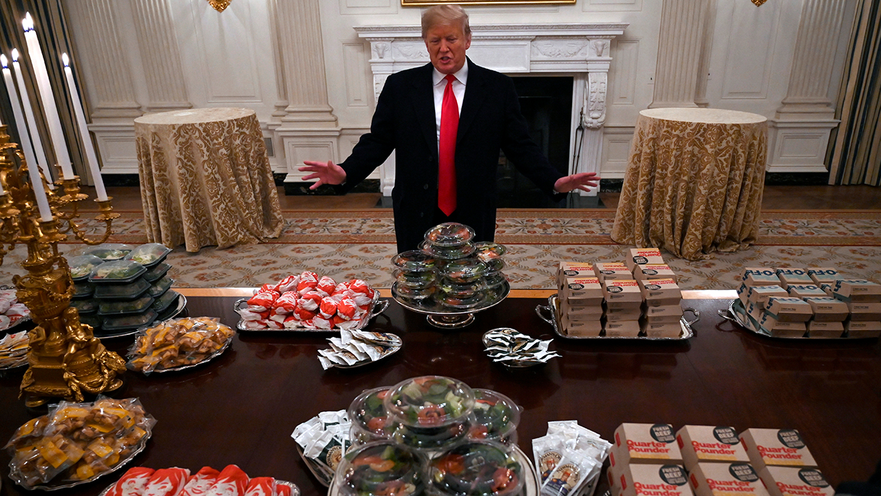President Donald Trump talks to the media about the table full of fast food in the State Dining Room of the White House for the reception for the Clemson Tigers.