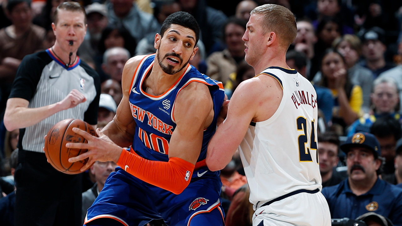 New York Knicks center Enes Kanter, left, is defended by Denver Nuggets forward Mason Plumlee during the second half of an NBA basketball game Tuesday, Jan. 1, 2019, in Denver.