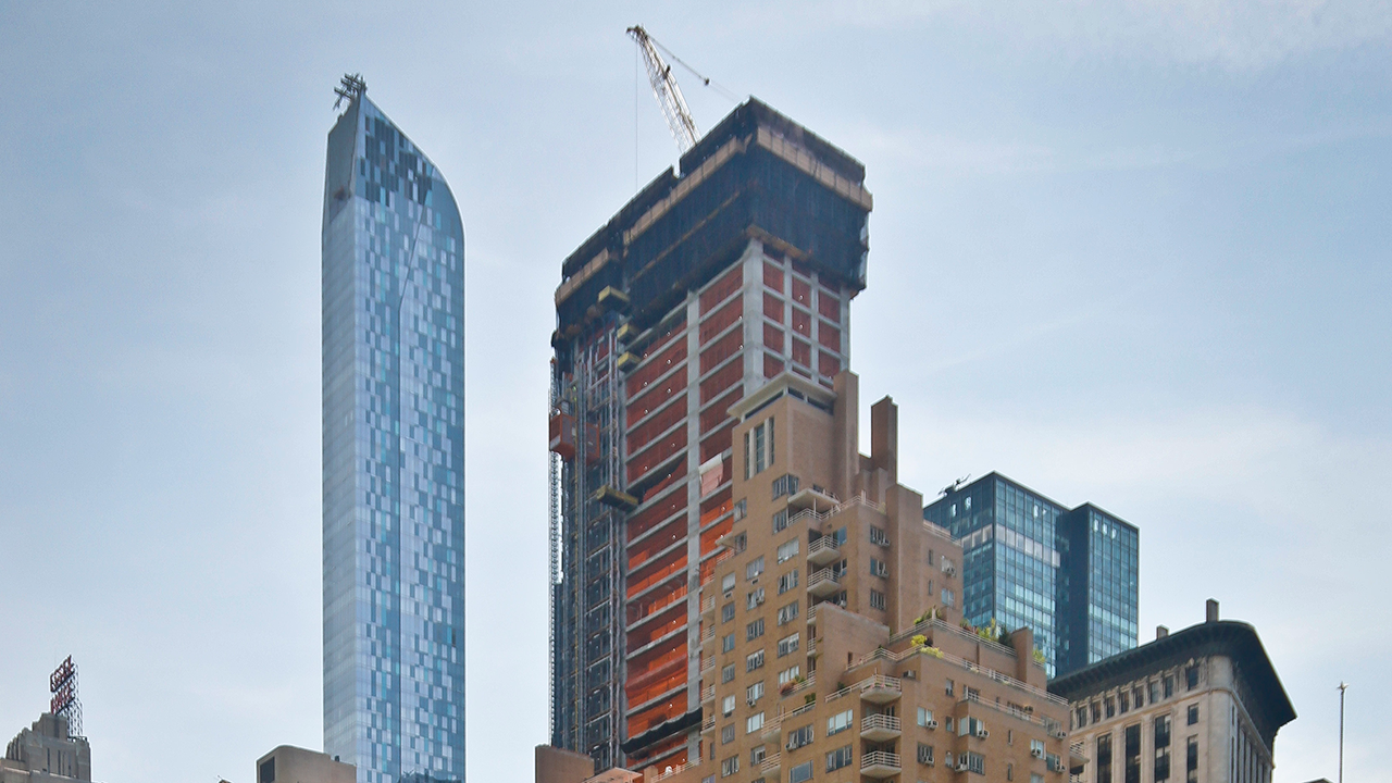 In this May 26, 2016 file photo, a crane sits atop ongoing construction for a new condominium skyscraper at 220 Central Park South in New York.