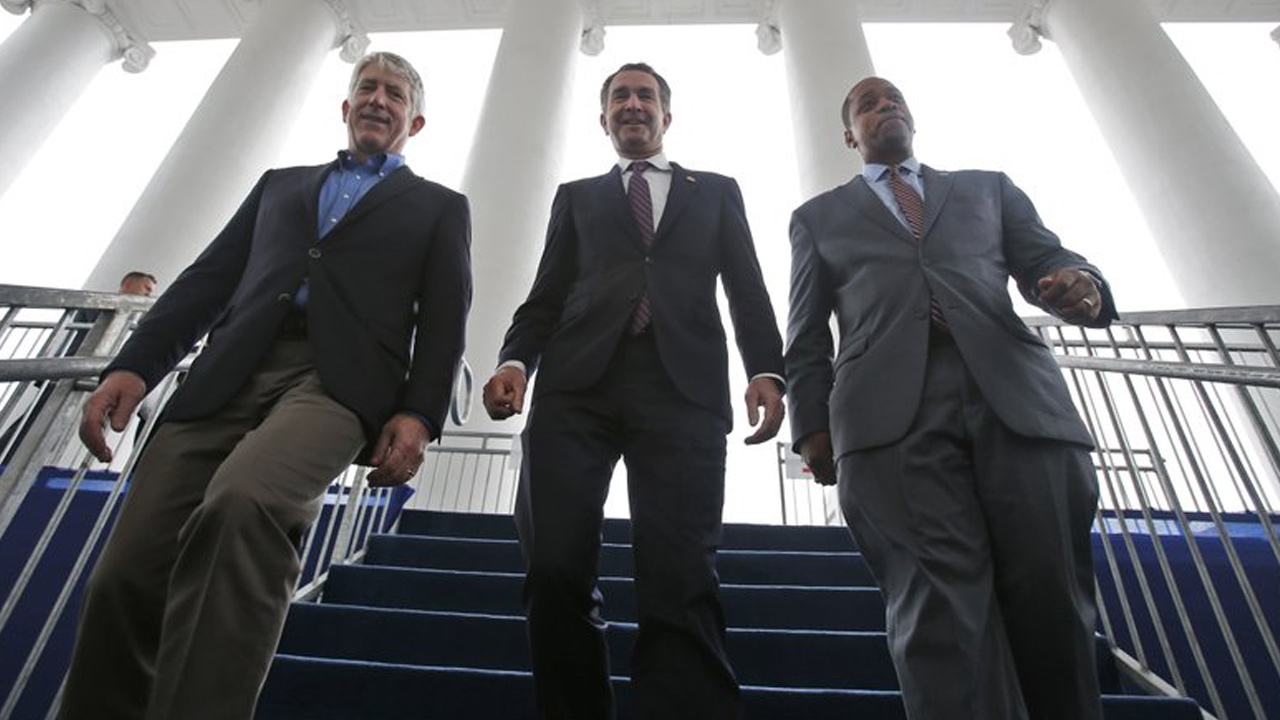 (FILE) Virginia Gov.-elect, Lt. Gov Ralph Northam, center, walks down the reviewing stand with Lt. Gov.-elect, Justin Fairfax, right, and Attorney General Mark Herring.