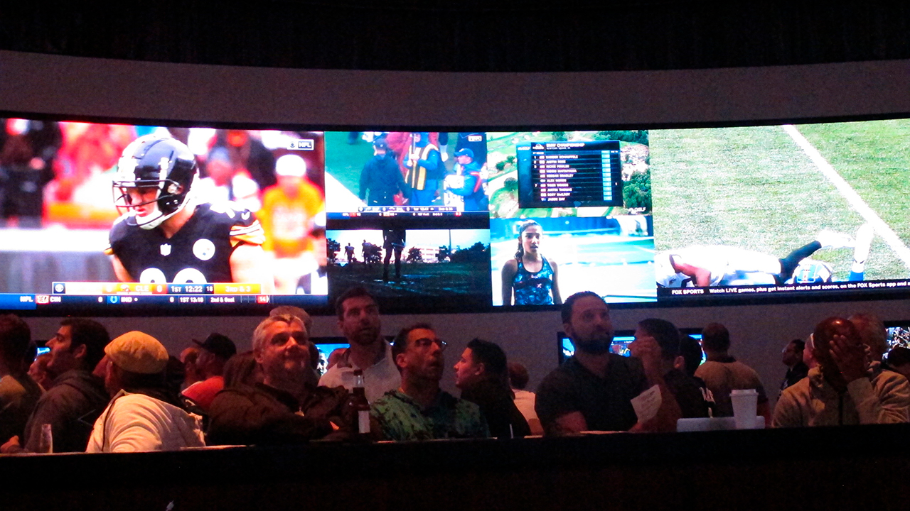 Football fans watch the action on wall-mounted video screens in the sports betting lounge at the Ocean Resort Casino in Atlantic City, N.J..