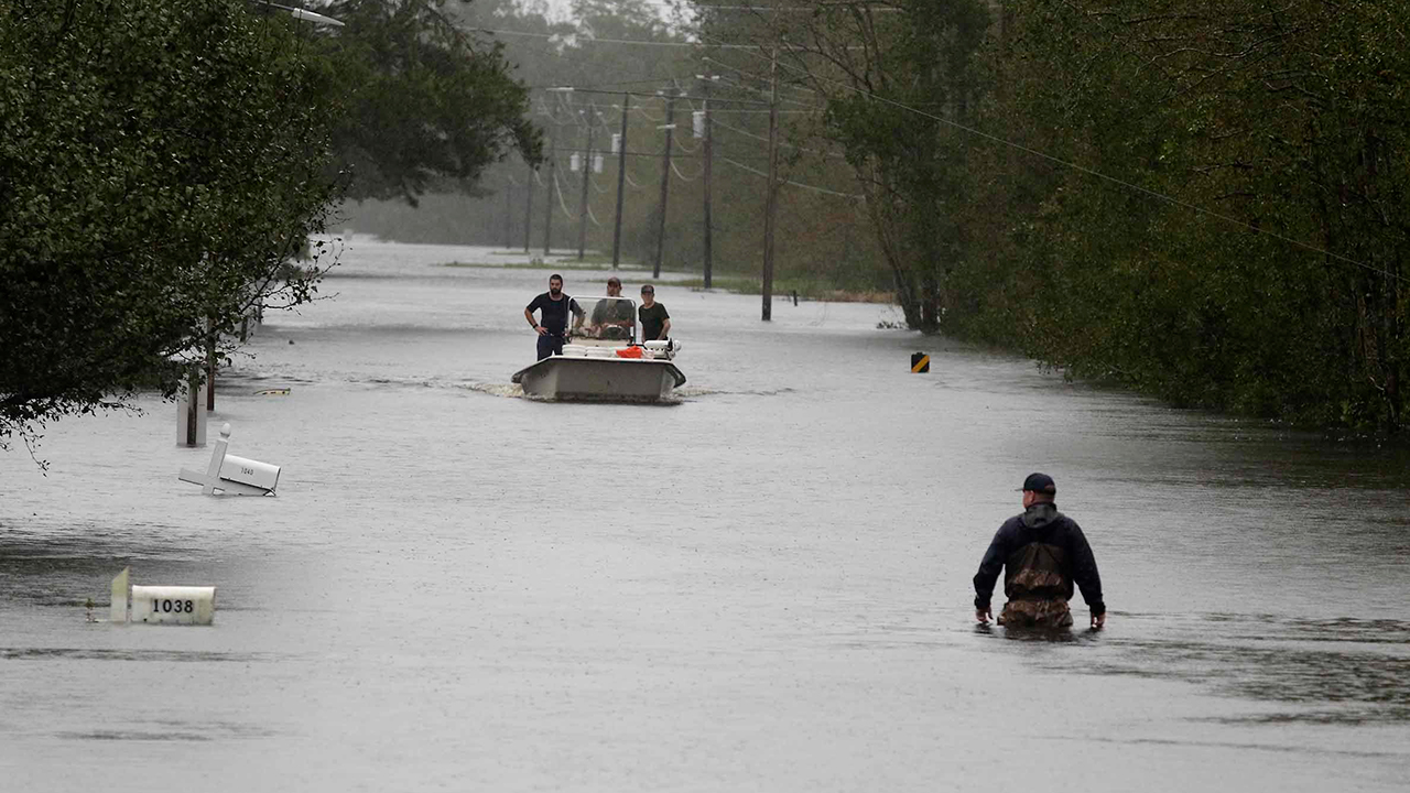A member of the U.S. Coast Guard walks down Mill Creek Road checking houses after tropical storm Florence hit Newport N.C., Saturday, Sept. 15, 2018.
