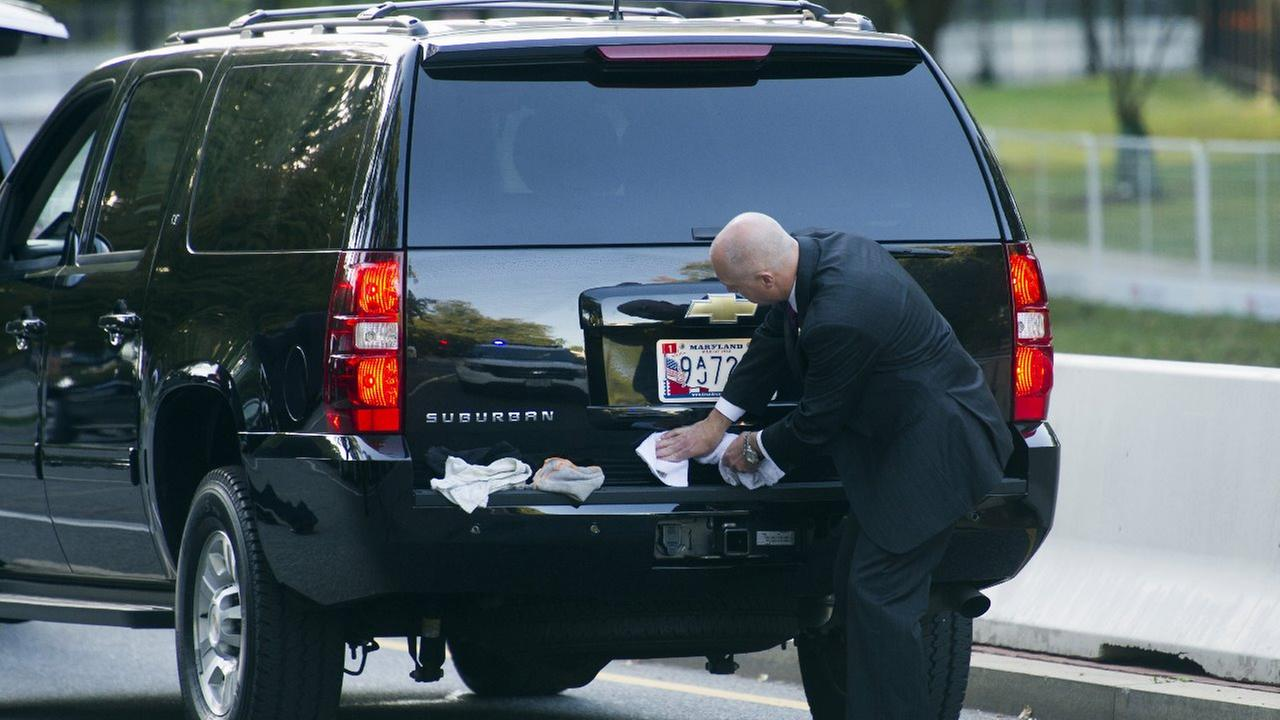 A Secret Service Agent wipes-down a motorcade vehicle as he waits for Pope Francis departure from the Apostolic Nunciature, the Vaticans diplomatic mission in Washington.