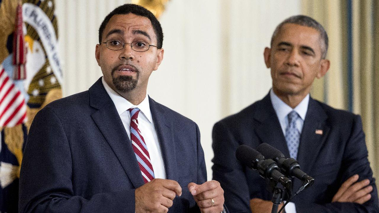 Senior Education Department official, John King Jr., left, accompanied by President Barack Obama, speaks in the State Dining Room of the White House in Washington, Friday, Oct. 2.