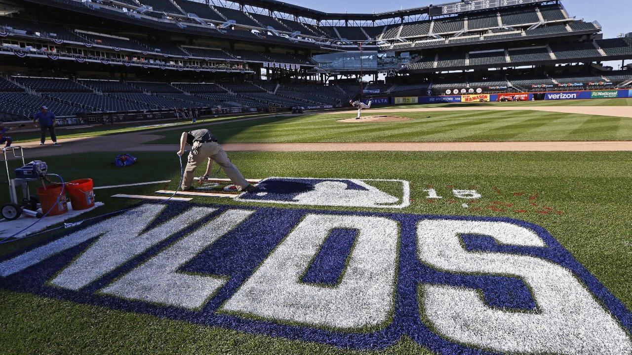 A worker paints the National League Division Series logo on the field as New York Mets Game 4 starter Steven Matz prepares to throw from the mound on Sunday, Oct. 11, 2015.