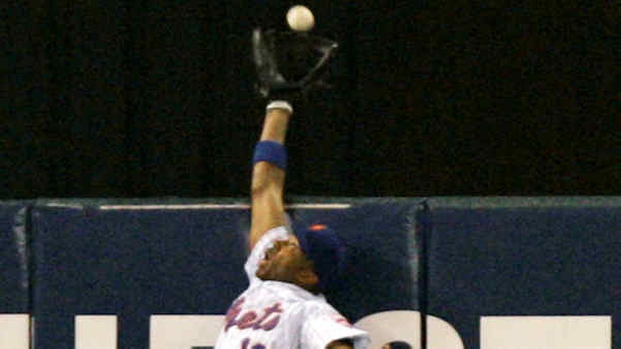 Endy Chavez makes a leaping catch at the wall to take away a home run away from St. Louis Cardinals Scott Rolen during the sixth inning of Game 7 of baseballs NLCS.