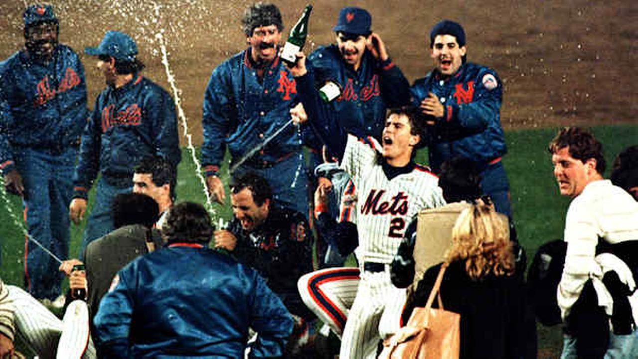 Kevin Elster and other members of the Mets spray champagne on the field at She Stadium, Monday night, Oct. 27, 1986.