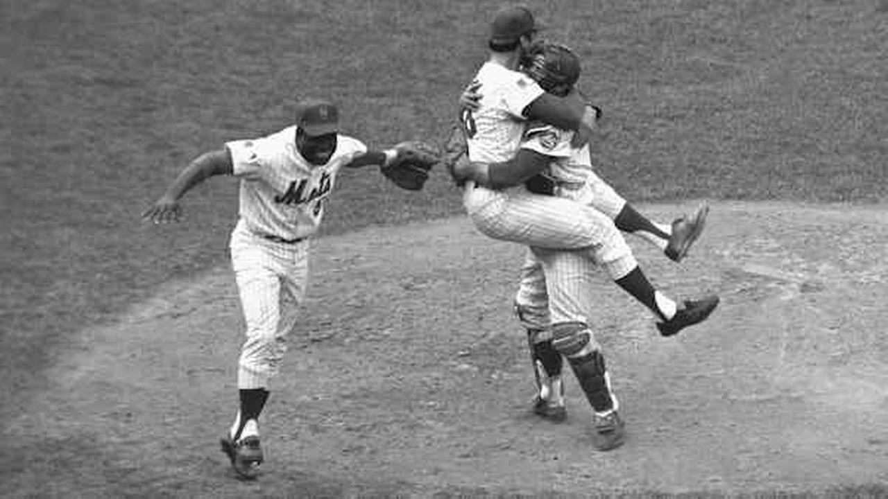 Catcher Jerry Grote embraces pitcher Jerry Koosman as the Mets defeat the Orioles in the fifth game to win the World Series at New Yorks Shea Stadium. At left is Ed Charles.