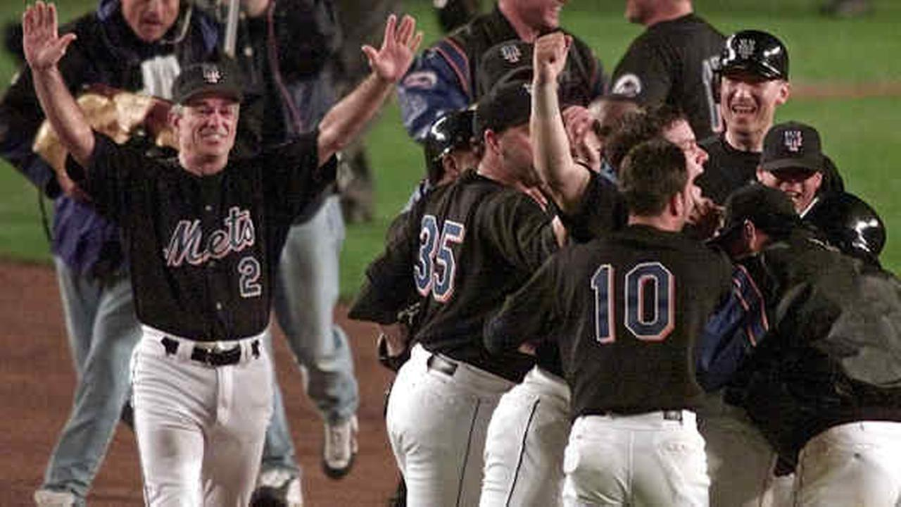 Manager Bobby Valentine throws his arms up as his team celebrates on the field after Mets Robin Venturas grand slam-turned single in the 15th inning.