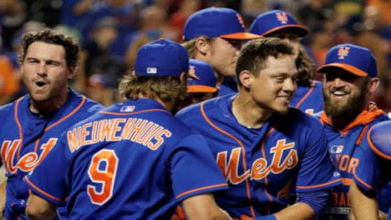 New York Mets Wilmer Flores, center, is mobbed by teammates after hitting a walkoff solo home run during the twelfth inning of a baseball game to defeat the Washington Nationals.