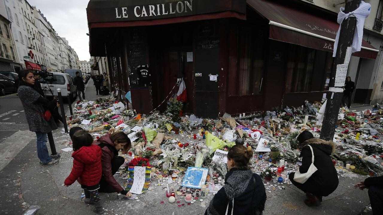People lay flowers and candles in front of the restaurant Le Carillon, one of the establishments targeted in Fridays gun and bomb attacks, in Paris, Monday, Nov. 16, 2015.