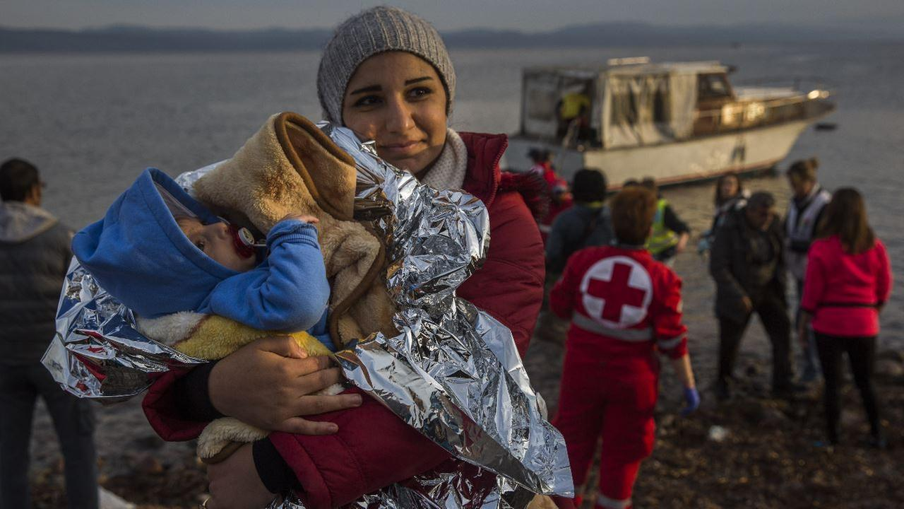 A Syrian woman holds her baby after their arrival on a small boat from the Turkish coast on the northeastern Greek island of Lesbos Monday, Nov. 16, 2015.