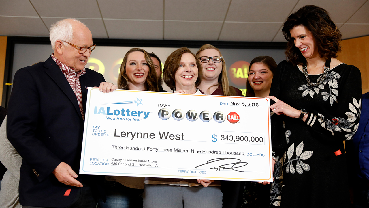 owa Lottery CEO Terry Rich, left, presents a check to Lerynne West, of Redfield, Iowa, center, for her share of a nearly $700 million Powerball prize.